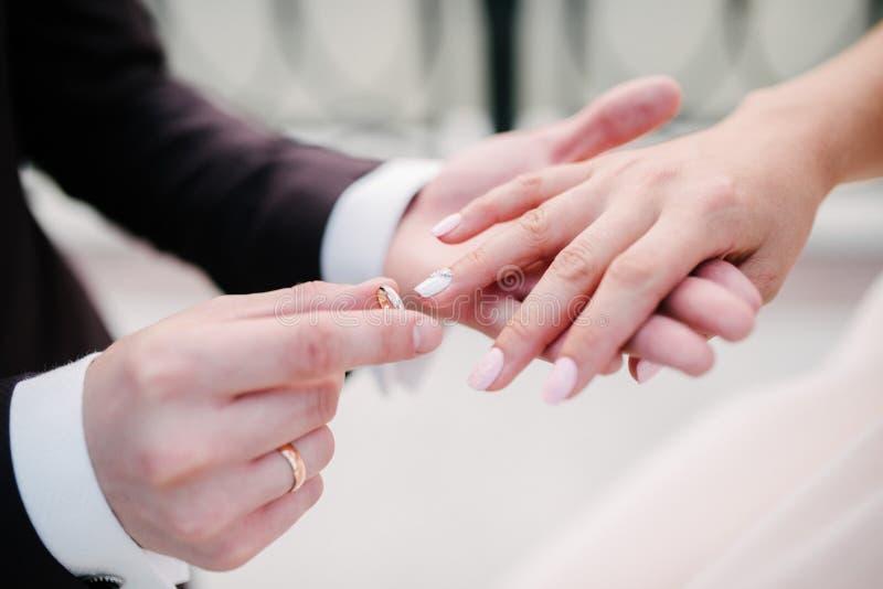 De bruidegom zet de trouwring op bruid dichte omhooggaand De bruid zet de bruidegom op de trouwring stock afbeelding