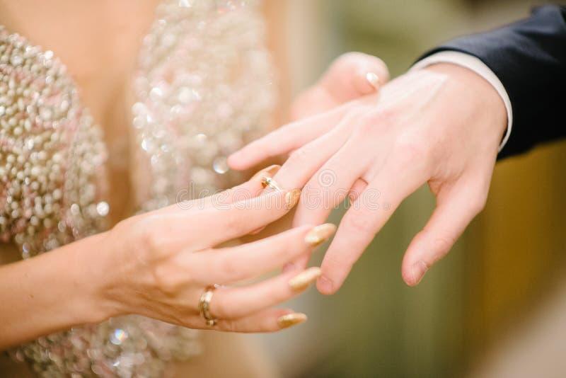 De bruidegom zet de trouwring op bruid dichte omhooggaand De bruid zet de bruidegom op de trouwring royalty-vrije stock afbeelding