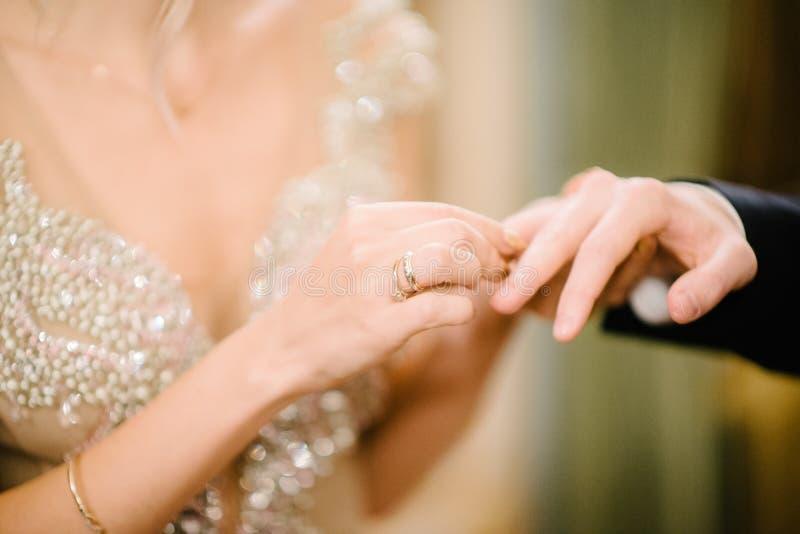 De bruidegom zet de trouwring op bruid dichte omhooggaand De bruid zet de bruidegom op de trouwring royalty-vrije stock fotografie