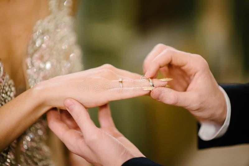 De bruidegom zet de trouwring op bruid dichte omhooggaand De bruid zet de bruidegom op de trouwring royalty-vrije stock afbeeldingen