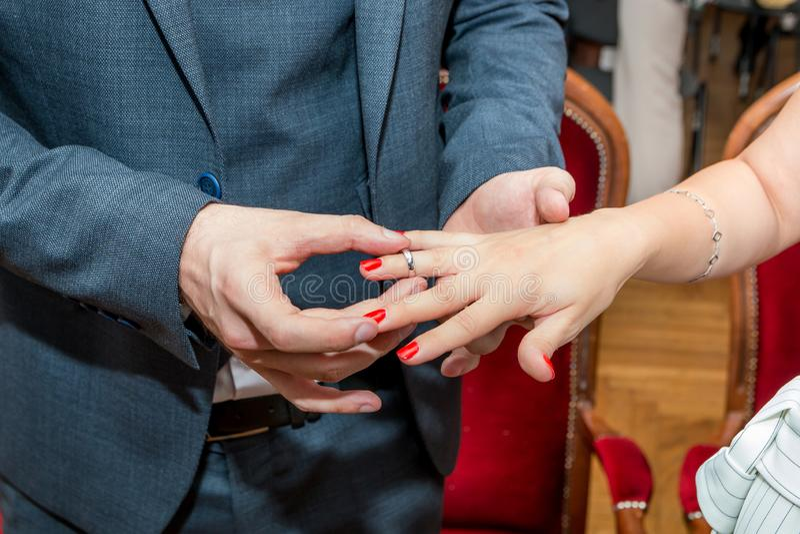 De bruidegom zet trouwring op bruid` s vinger stock afbeeldingen