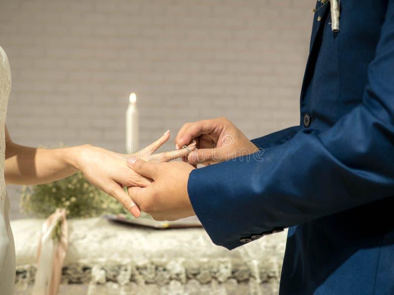 De bruidegom zet trouwring op bruid` s vinger in huwelijksceremonie stock afbeelding