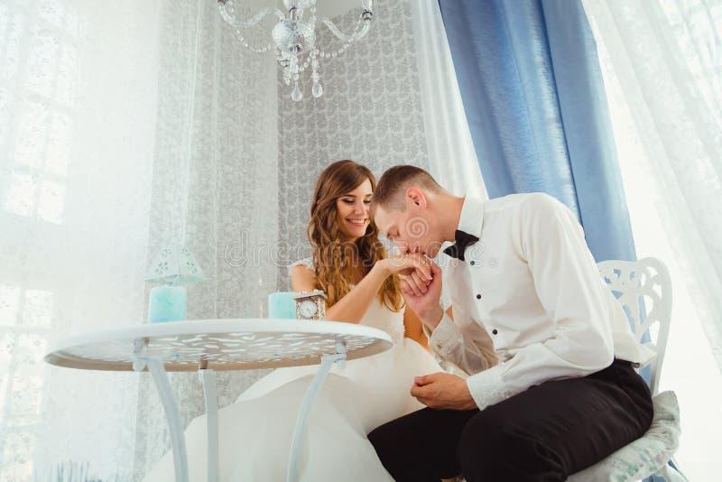 De bruidegom in zwarte vlinderdas kust bride& x27; s hand terwijl het zitten royalty-vrije stock afbeelding