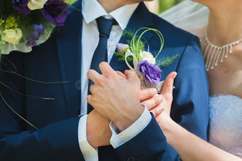De bruidegomechtgenoot, houdt zacht de hand van de bruidvrouw stock foto