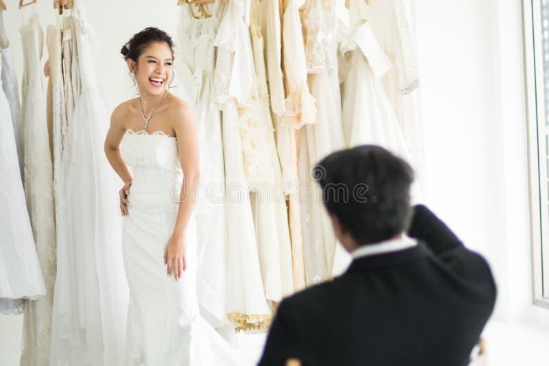 De bruidegomzitting en kijkt zijn Bruid die kleding proberen royalty-vrije stock afbeeldingen