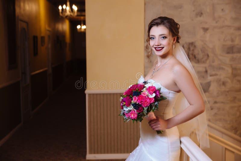 De bruidgangen rond het grote hotel, glimlacht en heeft pret, geniet van het aroma van haar bloemboeket royalty-vrije stock afbeelding