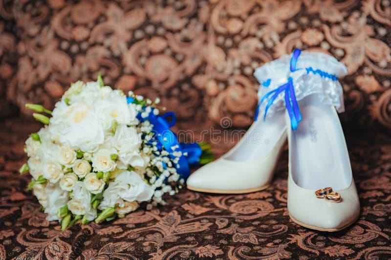 De bruidkouseband en ringen van huwelijksschoenen stock afbeelding