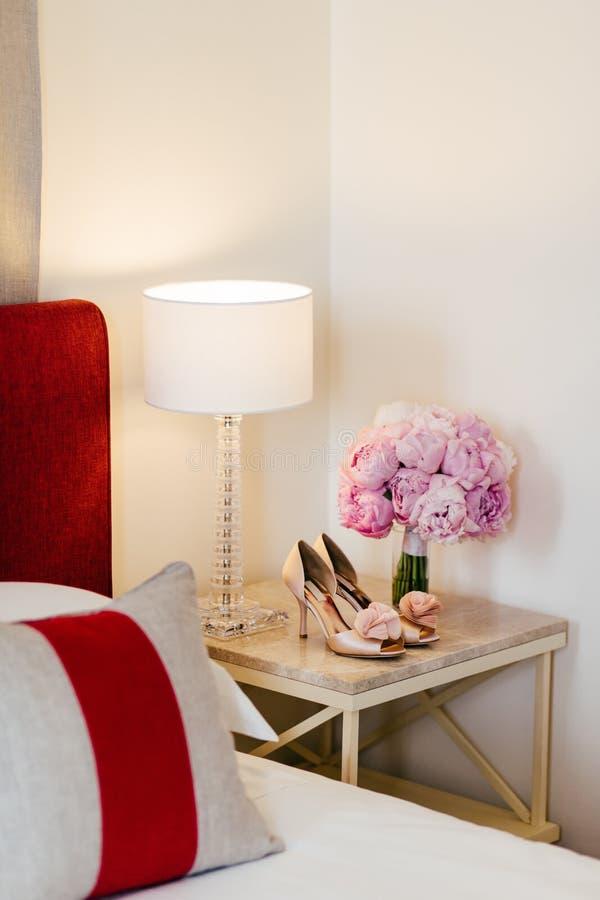 De bruids samenstelling van ochtenddetails Mooie bouquete van roze bloemen, huwelijksschoenen die op bed-lijst in slaapkamer stna royalty-vrije stock foto