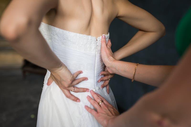 De bruidsmeisjehulp maakt een huwelijkskleding de bruid vóór de ceremonie vast Huwelijk Bruidsmeisje die bruid voorbereiden op de royalty-vrije stock fotografie