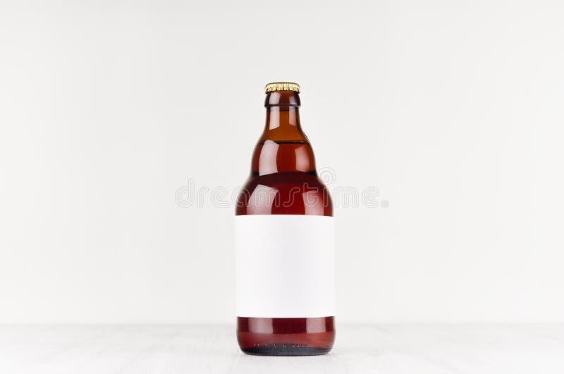 De bruine Belgische fles van het steiniebier 500ml met leeg wit etiket op witte houten raad, bespot omhoog stock afbeeldingen