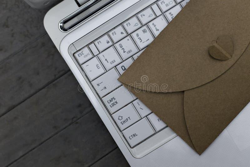 De bruine envelop legt op witte laptop op houten grijze achtergrond stock afbeelding