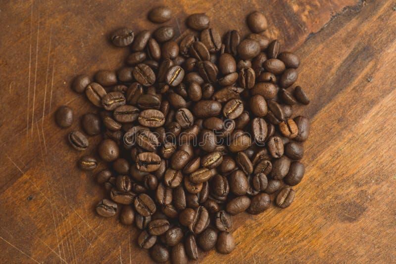 De bruine koffiebonen in cirkel vormen, close-up van macrokoffiebonen voor achtergrond en textuur Op bruine houten raad stock foto