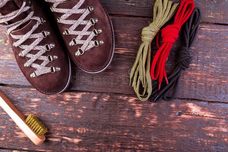 De bruine laarzen van het mensensuède met borstelschoenveters op houten achtergrond De herfst of de winterschoenen royalty-vrije stock afbeeldingen