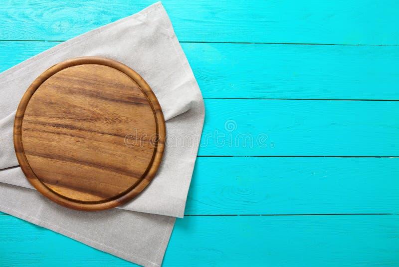 De bruine ronde scherpe raad van het pizzavoedsel voor vakantieschotels op grijs linnentafelkleed Blauwe houten achtergrond in re stock fotografie