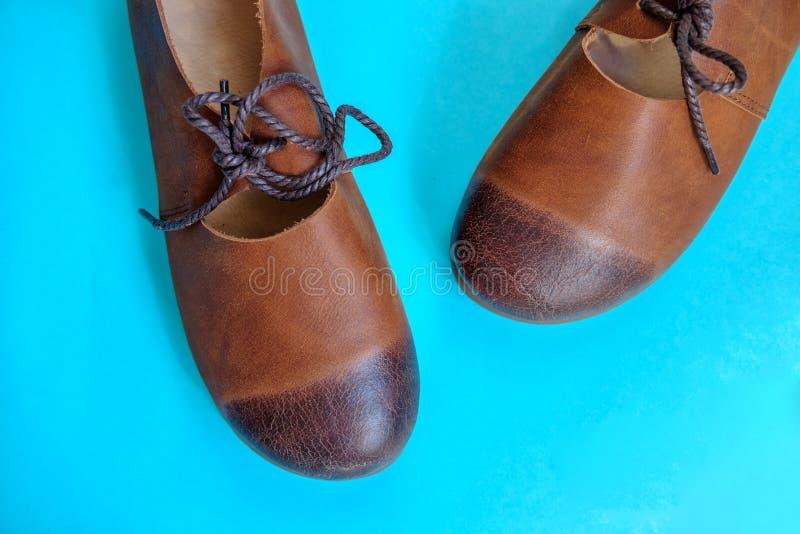De bruine schoenen van het vrouwen` s leer op blauwe achtergrond royalty-vrije stock fotografie