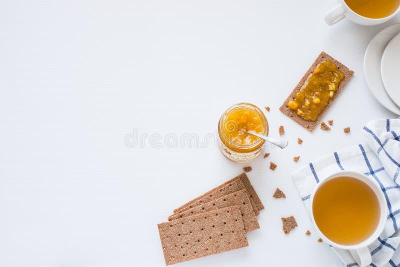 De bruine Zweedse crackers van het rogge knapperige brood met oranje die jam en stukken van sinaasappel, met koppen met aftreksel royalty-vrije stock foto's