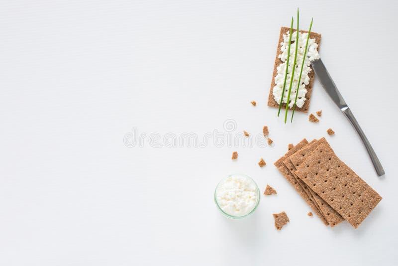 De bruine Zweedse crackers van het rogge knapperige brood met uitgespreide die kwark, met dunne groene ui, op witte achtergrond w stock afbeelding