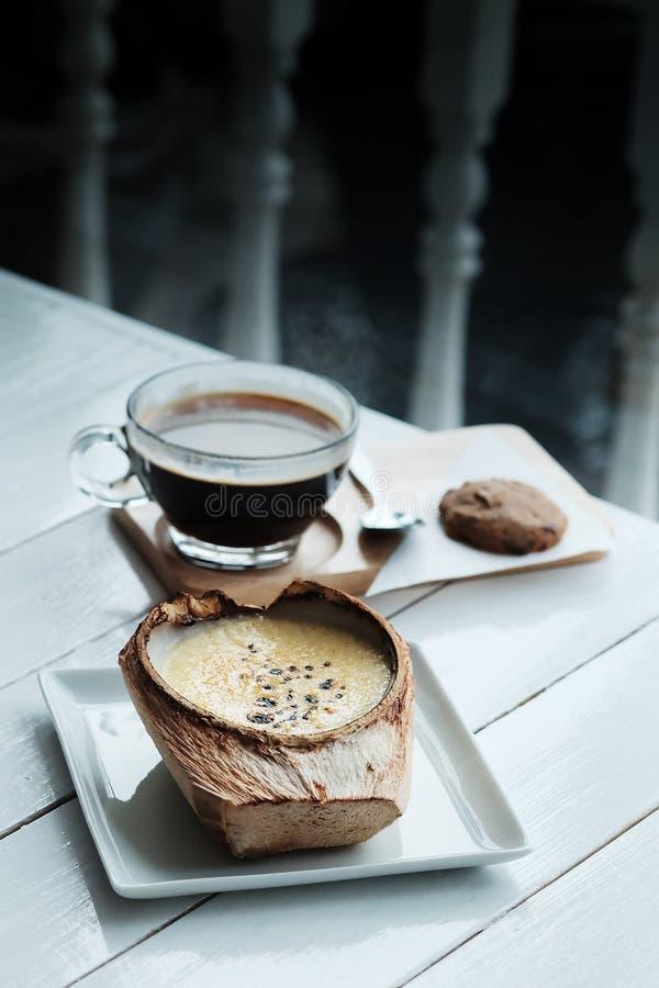 De Brulee Kokosnotenroom is suikerachtige aroma's en drank met hete americano zwarte koffie op witte houten lijstachtergrond stock foto's