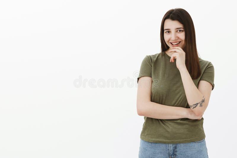 De brutale creatieve en slimme vrouw heeft het interessante idee smirking van vreugde en renteholdingshand op kin kijkend geamuse stock foto