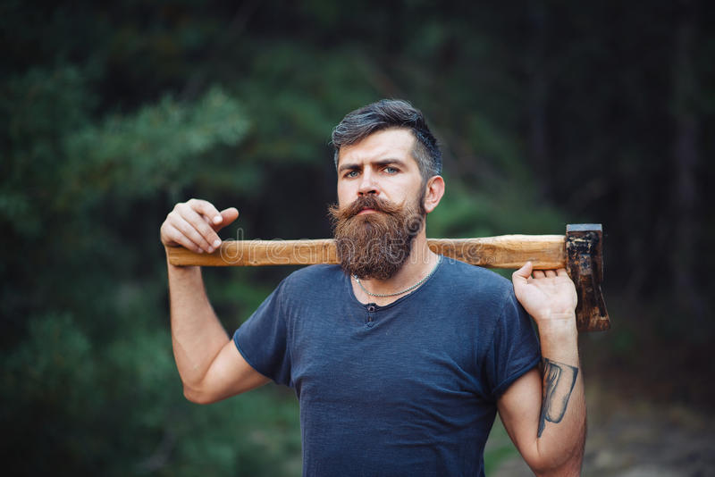 De brutale gebaarde mens met een slimme snor met een bijl in van hem dient het hout in stock fotografie
