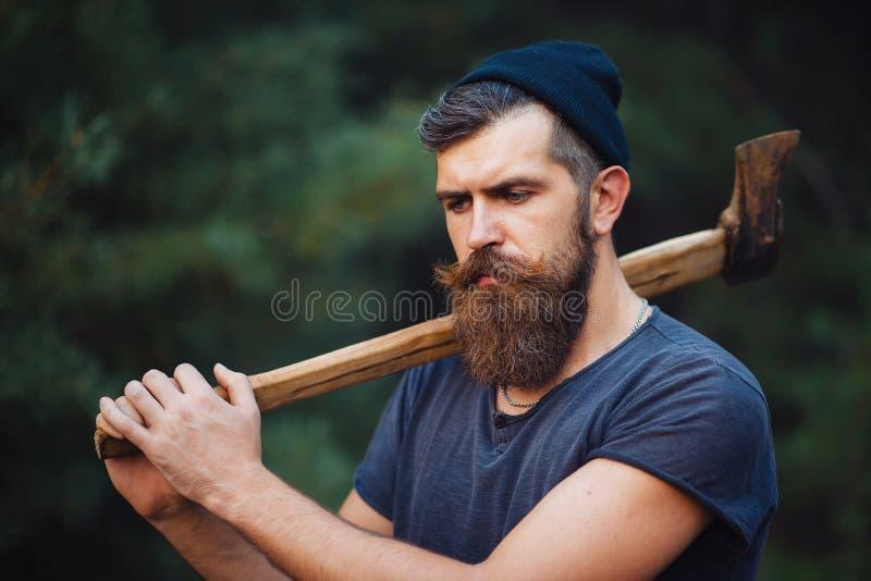 De brutale gebaarde mens met een slimme snor met een bijl in van hem dient het hout in stock foto