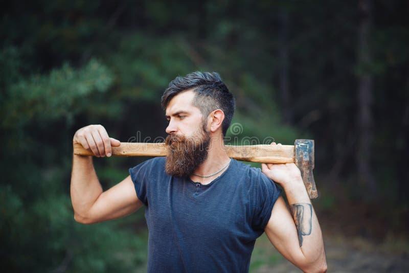 De brutale gebaarde mens met een slimme snor met een bijl in van hem dient het hout in royalty-vrije stock foto