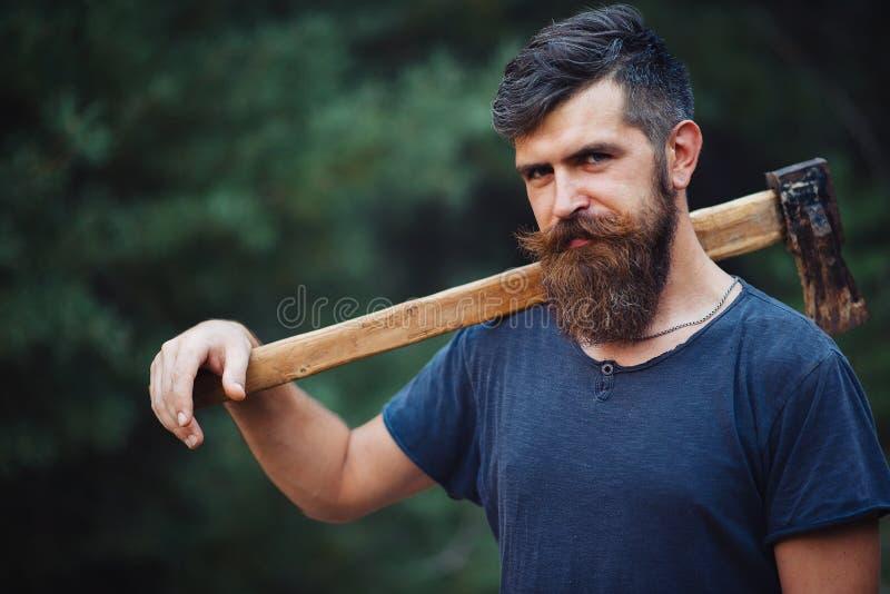 De brutale gebaarde mens met een slimme snor met een bijl in van hem dient het hout in royalty-vrije stock afbeelding