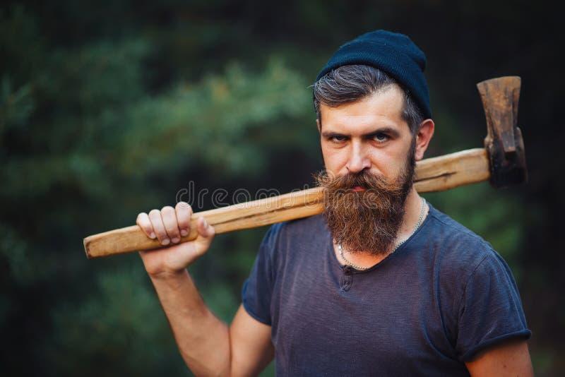 De brutale gebaarde mens met een slimme snor met een bijl in van hem dient het hout in royalty-vrije stock fotografie