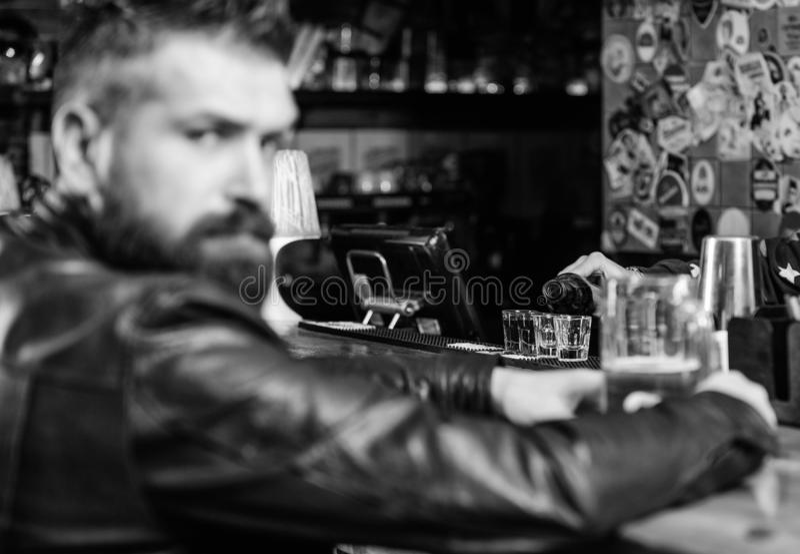 De brutale hipster gebaarde mens zit bij barteller drinkt bier Vrijdag avond De bar ontspant plaats om drank te hebben en te onts royalty-vrije stock afbeelding