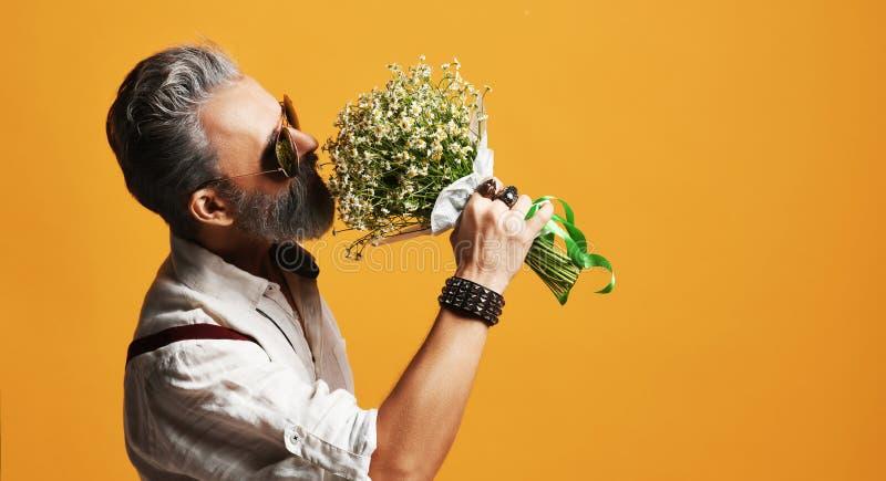 De brutale hogere gebaarde oude mens in vliegenierszonnebril ruikt een bos van bloemen stock foto