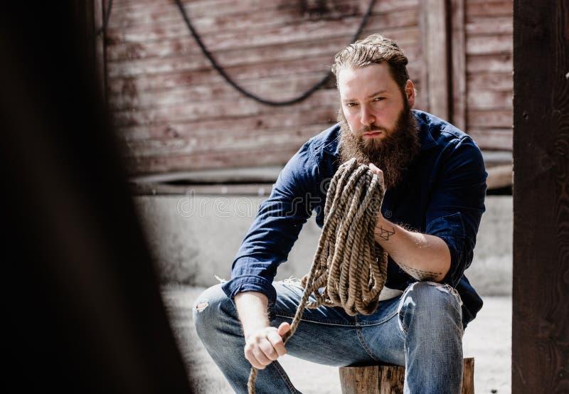De brutale mens met een baard gekleed in vrijetijdskleding met tattos op zijn handen houdt een rol van kabel naast de houten muur royalty-vrije stock afbeeldingen