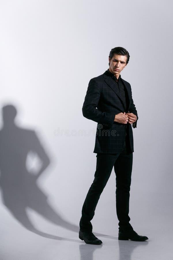 De brutale mens in volledig kostuum, stelt met attitudine, die op een witte achtergrond wordt ge?soleerd Binnen geschotene vertic stock foto