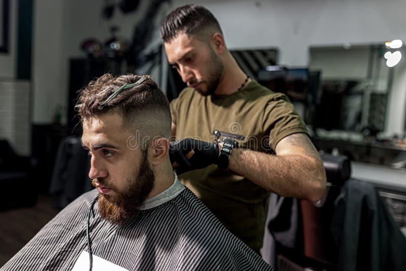 De brutale mens zit als voorzitter bij een kapperswinkel De kapper in zwarte handschoenen scheert man haren bij de rug royalty-vrije stock foto's