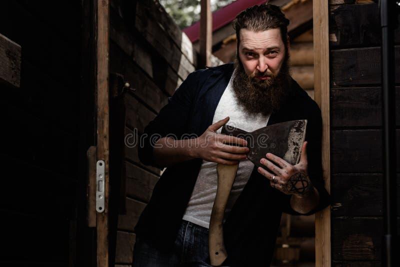 De brutale sterke mens met een baard gekleed in vrijetijdskleding houdt de bijl in zijn handen die zich in de deuropening bevinde stock foto