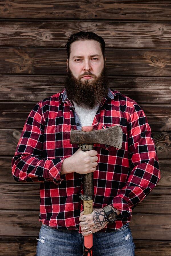 De brutale sterke mens met een baard kleedde zich in een gecontroleerd overhemd en gescheurde jeanstribunes met een bijl in de ha royalty-vrije stock foto