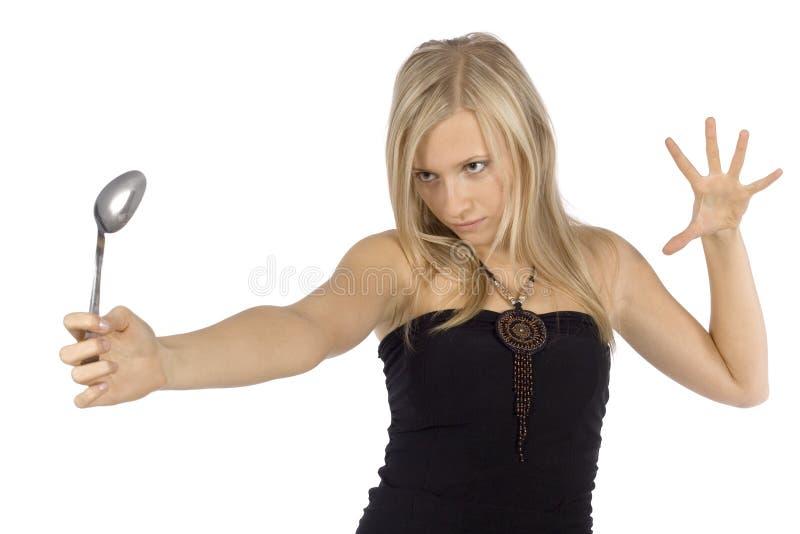 De buigende lepel van de vrouw door meningskracht stock afbeelding