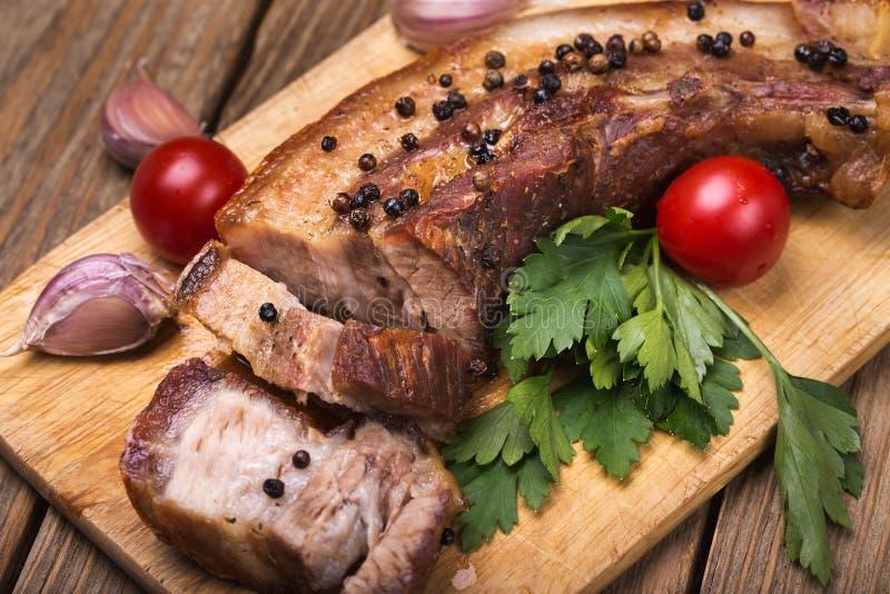 De buik van het braadstukvarkensvlees met kruiden op een houten raad stock foto's