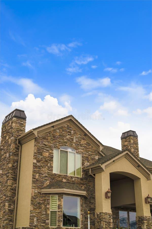 De buitenkant van een schitterend huis met een combinatie van steen en conrete ommuurt stock foto