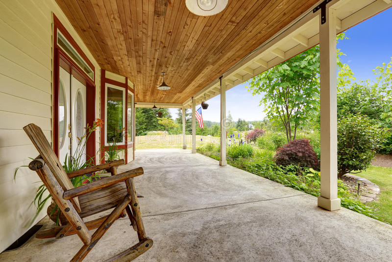 De buitenkant van het landbouwbedrijfhuis Ingangsportiek met schommelstoel stock foto