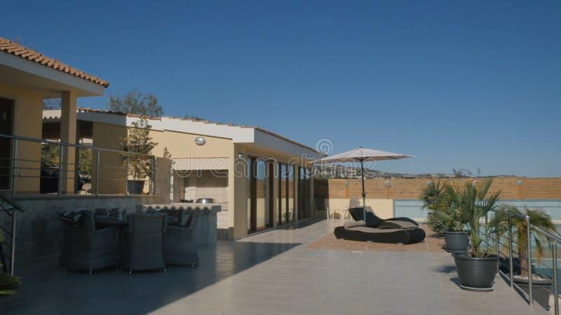 De buitenkant van moderne villa met terras zwembad en ligstoel