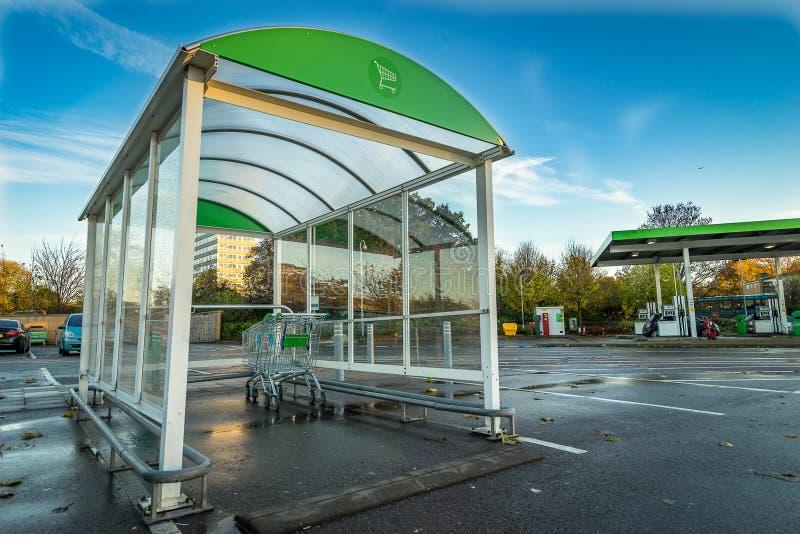 De buitenkant van supermarktkarretjes superstore in Stevenage en benzinepost op de achtergrond Het punt van de boodschappenwagent stock afbeelding