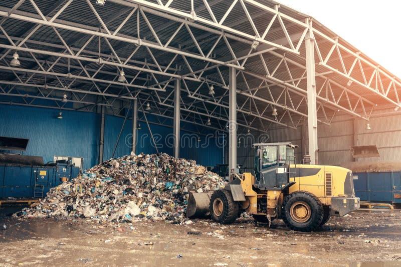 De bulldozer zal de afvalstortplaats schoonmaken De verwerkingsinstallatie van het afval Technologisch proces Zaken voor het sort stock fotografie