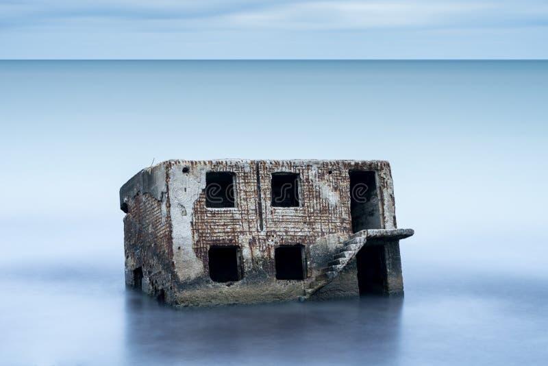 De bunker van het Liepajastrand Baksteenhuis, zacht water, golven en rotsen Verlaten militaire ruïnesfaciliteiten in een stormach stock foto's