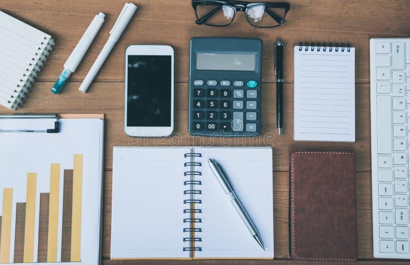 De bureaulevering en het lege notitieboekje op houten achtergrond stock foto