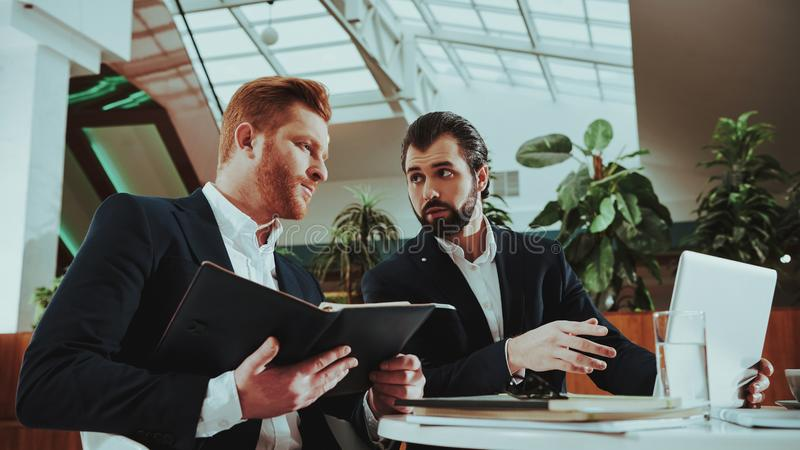 De bureaumanagers in Kostuum vergelijken Gegevens over Laptop stock fotografie