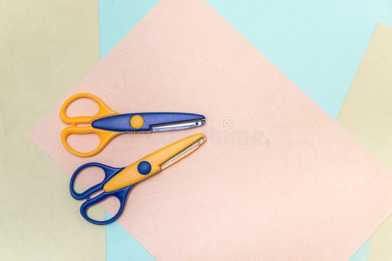 De bureauschaar blauw en geel voor school en handhandwerk, ligt op gekleurde bladen van document Het concept creativiteit, stock afbeelding