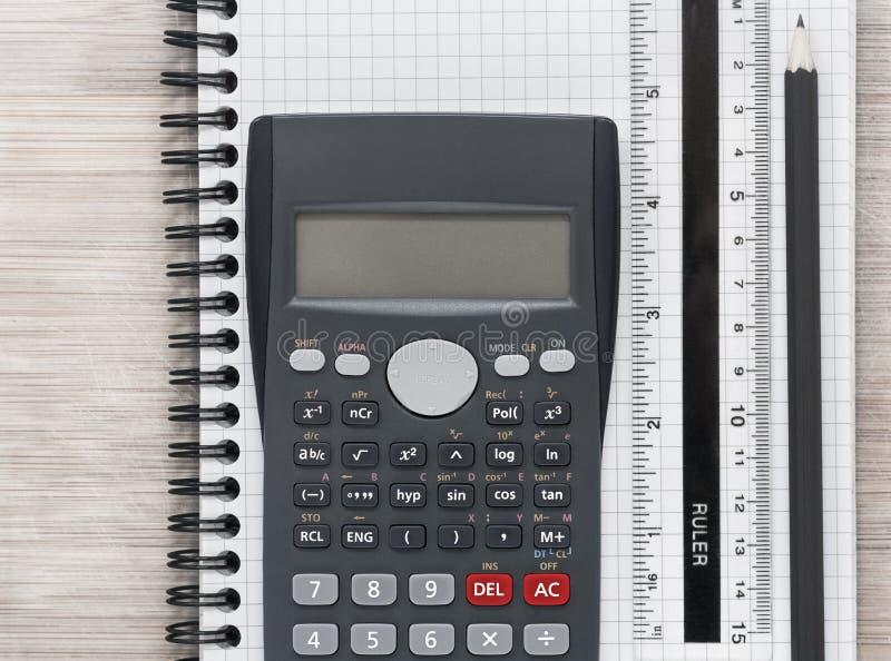 De bureauvlakte legt met calculator, heerser en potlood op een notitieboekje stock afbeelding