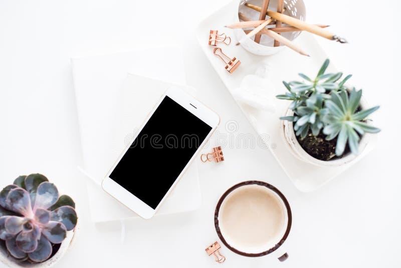 De bureauvlakte legt met coffe, smartphone en succulents, clea stock afbeeldingen