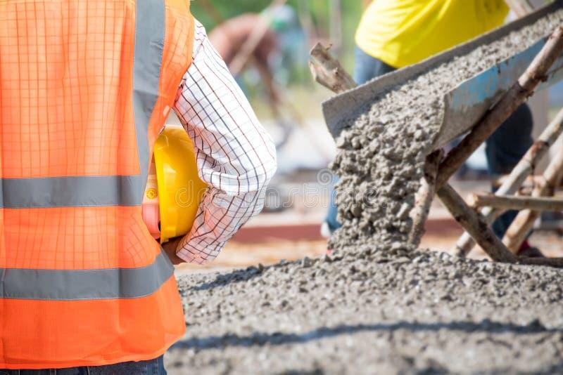 De Burgerlijke bouwkunde controleert het Concrete gieten tijdens commerciële concreting vloeren van de bouw royalty-vrije stock foto