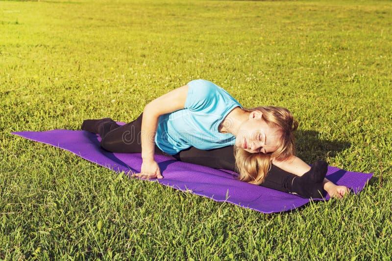 De bus van de blondevrouw in een sportieve korte bovenkant en gymnastiekbeenkappen maakt een brede streng op de deken want de yog royalty-vrije stock afbeelding